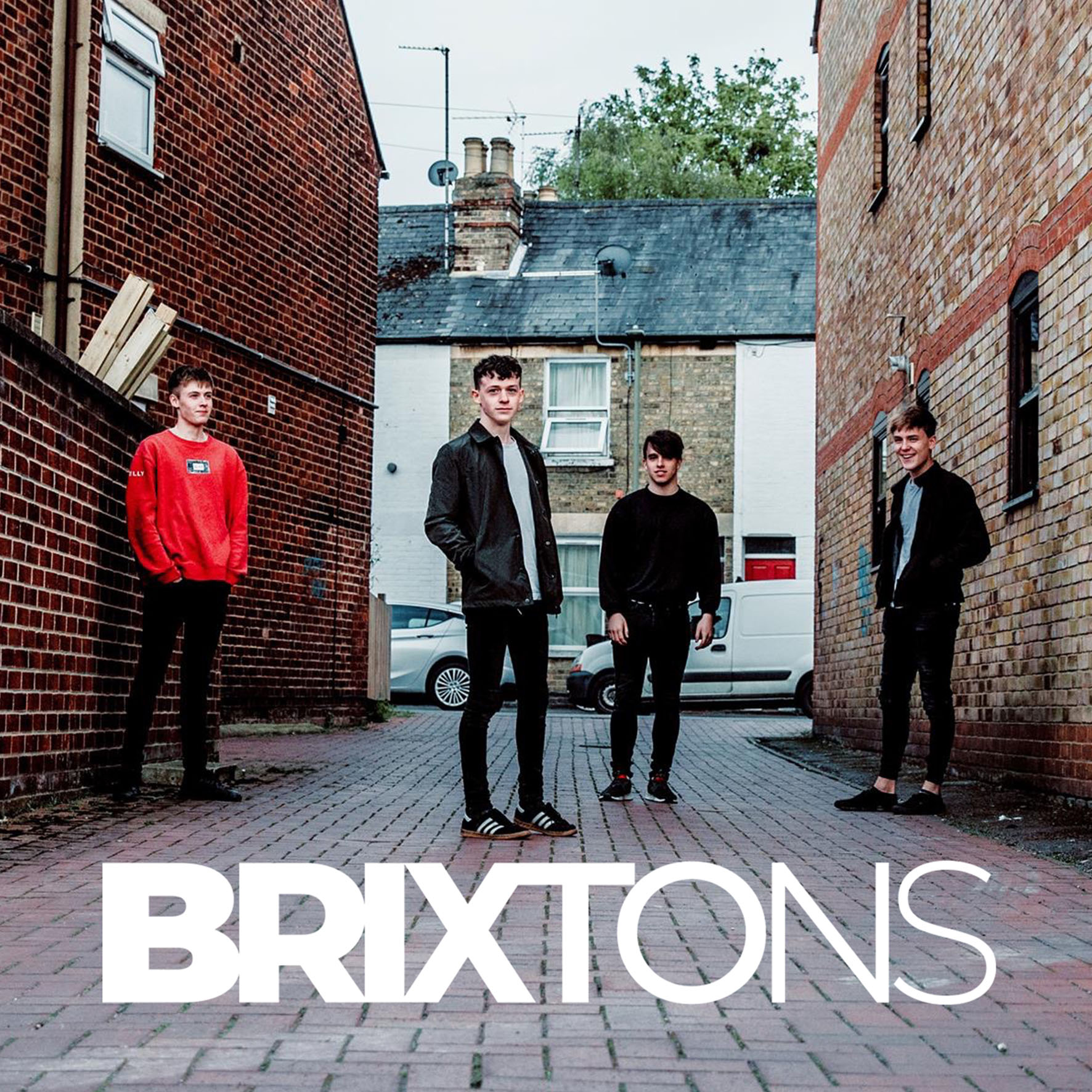 band members in alleyway with brixtons logo